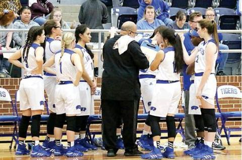 Photo by David Kapitan                                Lady Tiger players look on as Coach Dane Morgan draws up a play prior to the start of the third quarter against Ferris.