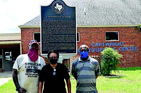Sylvester Spencer, Jr., Pat Wright and Tim Lowery stand in front of the historical marker that honors the legacy of the Cartwright School. The school, which has been converted to a community centre, is currently seeking donations to help repair the venue's air conditioning unit
